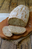 A loaf of homemade bread from whole grain  and rye flour whith sesame seeds on a wooden background. Copy space. Photographing with Stock Images