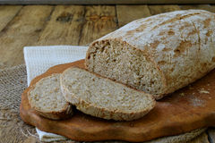 A loaf of homemade bread from whole grain  and rye flour whith sesame seeds on a wooden background. Copy space. Photographing with Royalty Free Stock Photo
