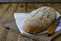 A loaf of homemade bread from whole grain  and rye flour whith sesame seeds on a wooden background. Copy space. Photographing with Stock Photography