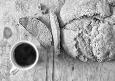 Loaf of homemade freshly baked bread and cup of coffee on the table. Closeup Royalty Free Stock Images