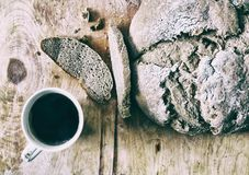 Loaf of homemade freshly baked bread and cup of coffee on the table. Closeup Royalty Free Stock Image