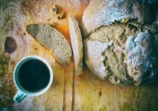 Loaf of homemade freshly baked bread and cup of coffee on the table. Closeup Royalty Free Stock Photos
