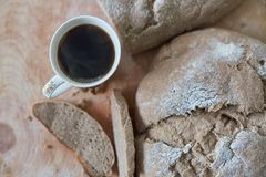 Loaf of homemade freshly baked bread and cup of coffee on the table. Closeup Royalty Free Stock Photography