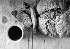 Loaf of homemade freshly baked bread and cup of coffee on the table. Closeup Stock Images