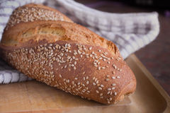 Loaf of Italian Bread. A loaf of crusty, seeded Italian bread served on a cutting board stock image