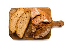 Loaf of rustic german bread on wooden board, isolated on white Royalty Free Stock Image