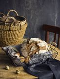 Loaf of rye bread in a basket with chicken eggs on the table. The Loaf of rye bread in a basket with chicken eggs on the table Royalty Free Stock Photo