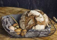 Loaf of rye bread in a basket with chicken eggs on the table. The Loaf of rye bread in basket with chicken eggs on the table Stock Images