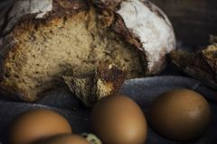 Loaf of rye bread with chicken eggs in wooden box. The Loaf of rye bread with chicken eggs in wooden box Stock Images