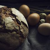 Loaf of rye bread with chicken eggs in wooden box, selective foc. The Loaf of rye bread with chicken and qual eggs, selective focus Stock Image