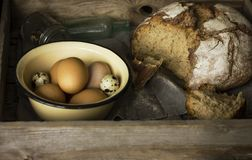 Loaf of rye bread with chicken and quail eggs in wooden box. The Loaf of rye bread with chicken and quail eggs in wooden box Stock Image