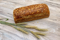 Loaf of rye bread and ears of wheat on the wooden background Royalty Free Stock Photo