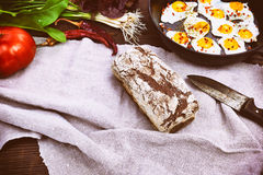 Loaf of rye bread and fried eggs in a black frying pan. Vintage toning Stock Photo