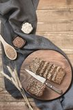 Loaf of rye bread sliced and ingredients on cutting board. Close up. Loaf of rye bread sliced and ingredients on cutting board, rural dark food background Royalty Free Stock Image