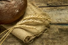 Loaf of rye bread with wheat ears on sackclothe Royalty Free Stock Photography