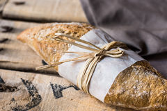 Loaf of rye whole wheat bread wrapped in parchment paper, linen napkin, vintage wood background Stock Photos