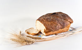 Loaf and slice of wheat bread with wheatears Stock Photos