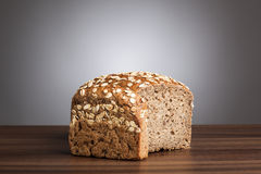 Loaf and slice of wholemeal bread on table Royalty Free Stock Photography