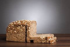 Loaf and slices of wholemeal bread on table Royalty Free Stock Image