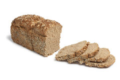 Loaf of spelt bread with sunflower seeds. Loaf of spelt bread and slices with sunflower seeds on white background Royalty Free Stock Photography
