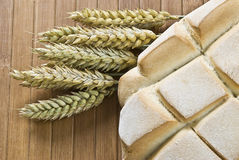 Loaf and wheat. A loaf and some wheat on a bamboo mat Royalty Free Stock Images