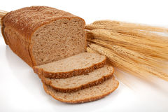 Loaf of wheat bread and shocks of wheat. A loaf of wheat bread and shock of wheat on a white background Stock Photos