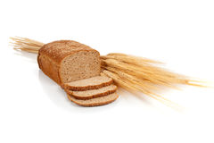 Loaf of wheat bread and shocks of wheat. A loaf of wheat bread and shock of wheat on a white background Stock Image