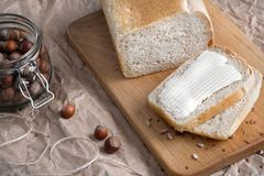 A loaf of wheat white bread, with a cut piece, lies on a wooden table and packing kraft paper. Next to the nuts in a. A loaf of wheat white bread, in a paper bag Stock Photo