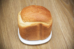 Loaf of white fresh bread on a plate on a wooden table Stock Photo