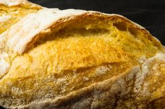 Loaf of white wheat bread. Fresh loaf of white wheat bread on black background stock images