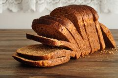 A loaf of whole wheat bread. Displayed on a wooden table Royalty Free Stock Photo