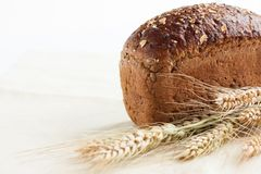 Loaf whole wheat bread and wheat ears Stock Photography