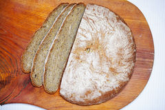 Loaf of wholegrain rustic bread sliced into portions Royalty Free Stock Photos