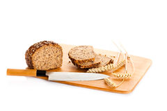 Loaf of wholemeal bread  cutting into slices on wood board isolated Stock Photo