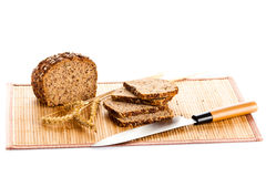 Loaf of wholemeal bread  cutting into slices on wood bread board Stock Images