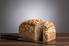 Loaf of wholemeal bread with knife on table Royalty Free Stock Image
