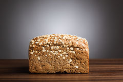 Loaf of wholemeal bread on table Stock Images