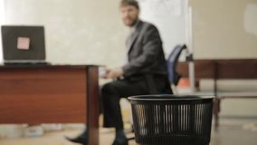 Loafer at office, businessman throws papers in trash can, dreams of vacation stock video