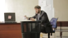 Loafer at office, businessman throws papers in trash can, dreams of vacation stock video footage