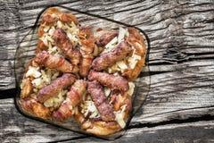 Loafs de carne grelhados Cevapcici rolado no bacon e nas coxas de frango servidos com a cebola na tabela de cozimento de vidro de Fotos de Stock
