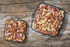 Loafs de carne grelhados Cevapcici rolado no bacon Rolls do bacon e da carne da galinha com a cebola desbastada nas bandejas de c Fotografia de Stock