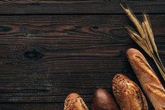 loafs de pão arranjados e de trigo na superfície de madeira Fotografia de Stock