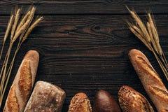 loafs de pão arranjados e de trigo na superfície de madeira Fotos de Stock