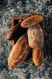loafs de pão arranjados na caixa de madeira no tabletop escuro com farinha Imagem de Stock
