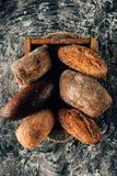loafs de pão arranjados na caixa de madeira no tabletop escuro com farinha Fotografia de Stock Royalty Free
