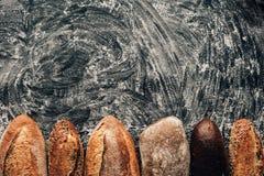 loafs de pão arranjados no tabletop escuro com farinha Imagens de Stock Royalty Free