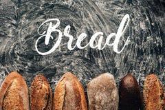 loafs de pão arranjados no tabletop escuro com rotulação da farinha e do pão Imagens de Stock