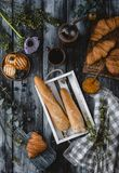Loafs de pão na caixa de madeira com croissant e de bebida ao redor no tabletop de madeira Fotografia de Stock