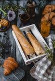 Loafs de pão na caixa de madeira com croissant e de bebida ao redor no tabletop de madeira Foto de Stock