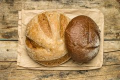 Loafs of different species of bread on wood background Stock Photos